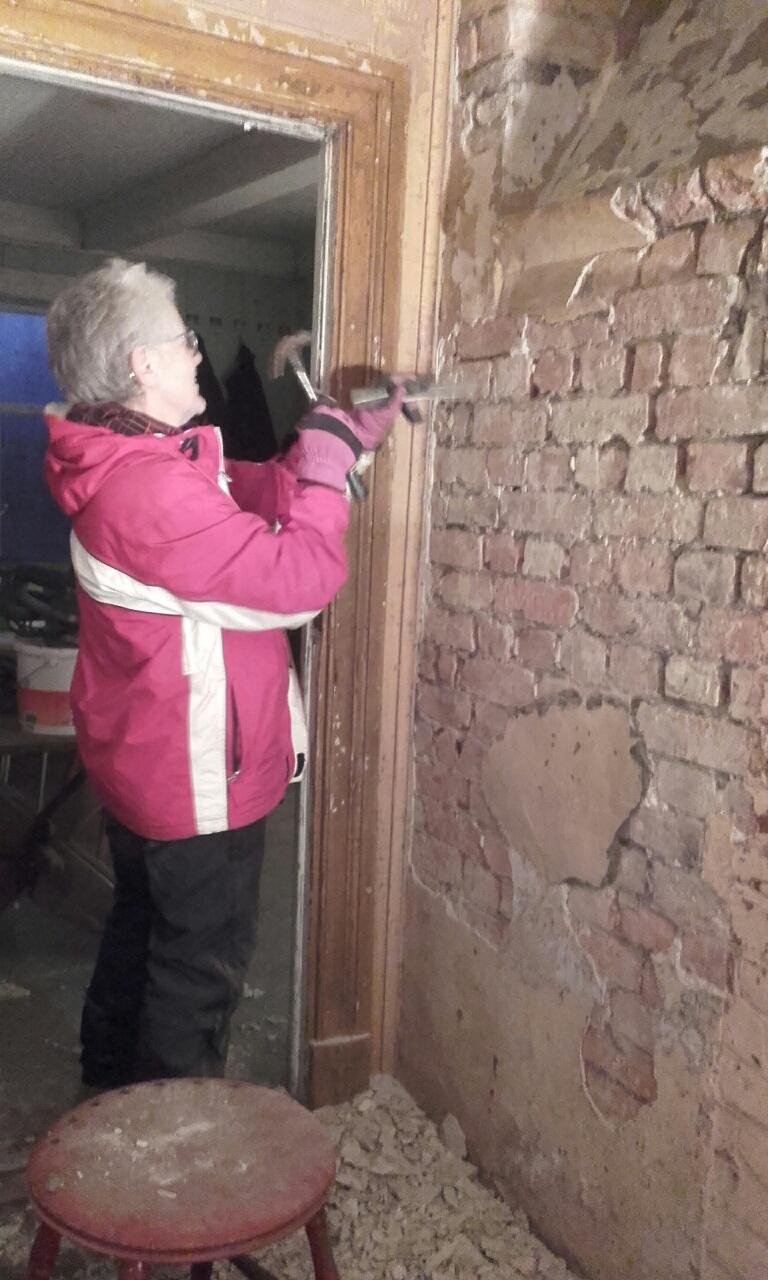 Ragnhild Nordengen fjerner gammel murpuss fra brannmuren